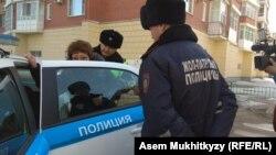 Жительницу Астаны Зауре Сагидолдину патрульные усаживают в полицейский автомобиль, 21 марта 2019 года.