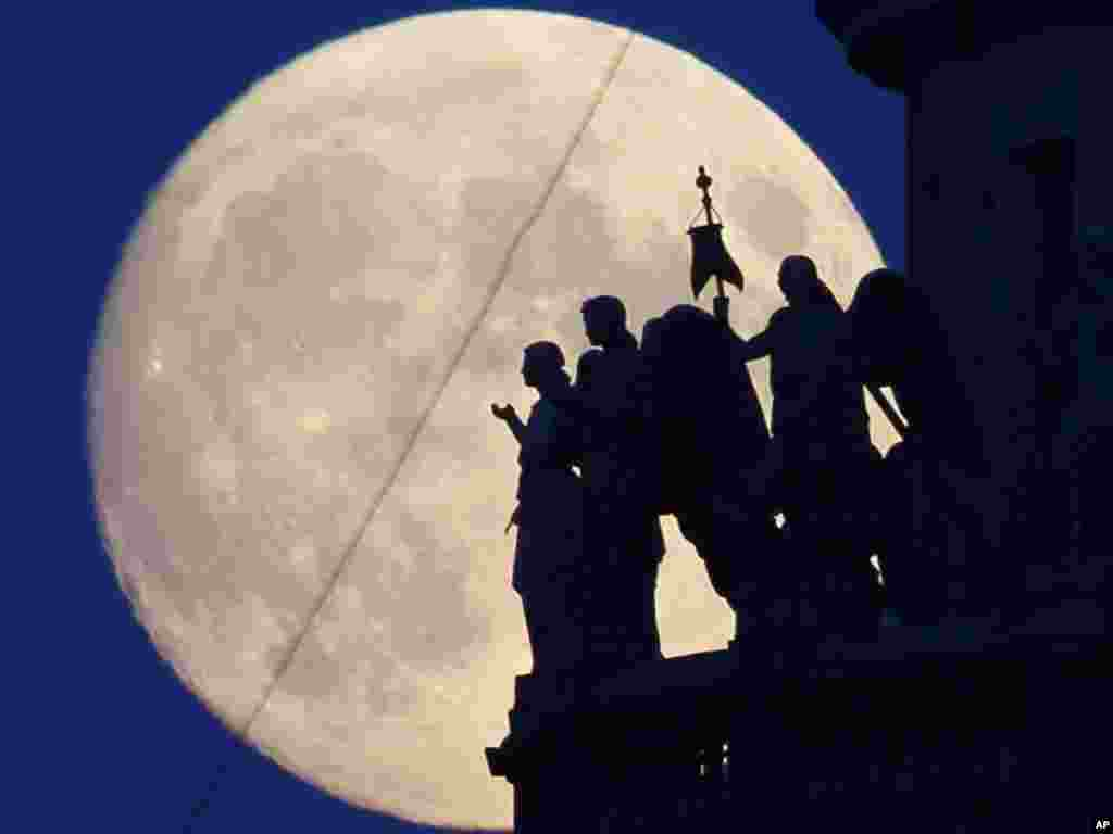 Statues of angels atop St. Isaak's Cathedral are silhouetted against the full moon in St. Petersburg, Russia, on June 15.Photo by Dmitry Lovetsky for AP
