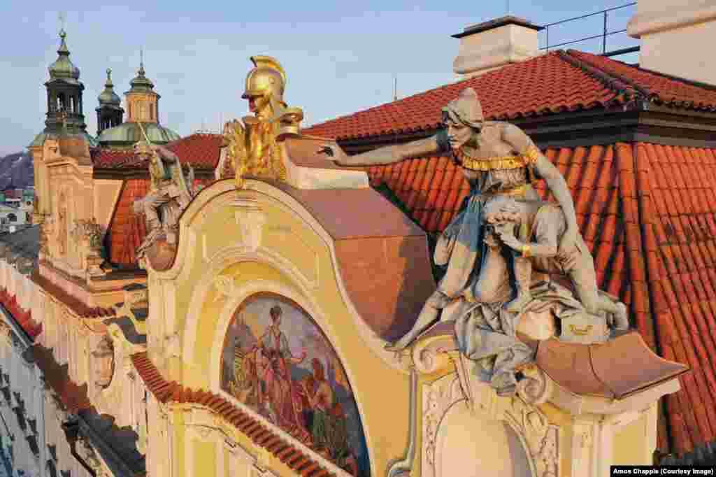 Втората фигура на покрива на старата пражка застрахователна компания изобразява жена и дете, които предупреждават хората за пожар. Скулптурата все още не е завършена, когато авторът ѝ Бохуслав Шнирх умира. По-късно тя е довършена от чирака му Ладислав Салоун.