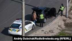 Поліцейський патруль перевіряє водія автомобіля у Києві, 26 березня 2020 року