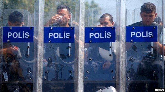 Police guard the entrance of Gezi Park on Taksim Square in Istanbul on June 17.
