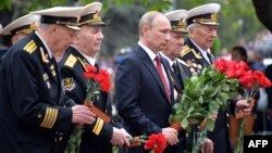 Russian President Vladimir Putin (center) and World War II veterans lay flowers at a war memorial in the Crimean port of Sevastopol on May 9.