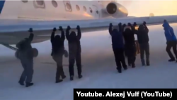 Krasnoyarsk, Igark. Men push the plane, which is frozen to the runway. 26 Nov 2014