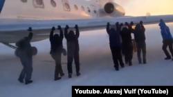 Njerëzit duke e shtyrë aeroplanin në qytetin Igark