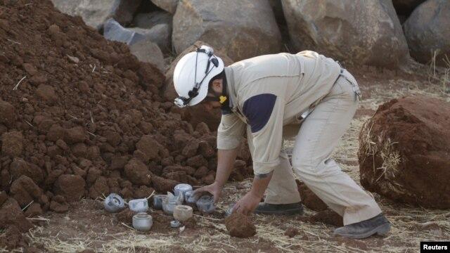 Гражданский сотрудник собирает неразорвавшиеся снаряды в сирийской провинции Идлиб, октябрь 2015 года