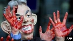 """Тони Блэрдің Ирактағы әскери операцияны іске асырушылардың бірі болғанына наразы жұрт оның маскасын аузы мен қолына """"қан жағып"""" киіп шықты. Лондон, 24 қараша 2009 жыл."""