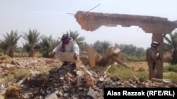 عراقي يجلس على أنقاض منزله بعد أن فجره مسلحون متطرفون في بابل.