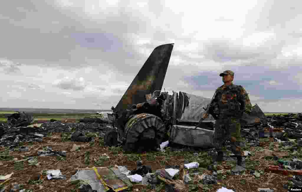 An armed pro-Russian separatist guards the crash site one day after an IL-76 Ukrainian army transport plane was shot down by anti-Kyiv militants in Luhansk, killing all 49 troops aboard. (Reuters/Shamil Zhumatov)
