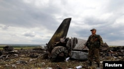 Пророссийский активист стоит у обломков военно-транспортного самолета Ил-76, подбитого сепаратистами при заходе на посадку в аэропорту Луганска 14 июня.