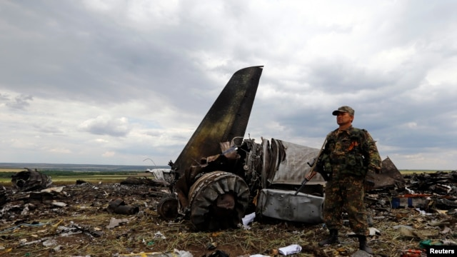 An armed pro-Russian separatist stands guard at the site of the crash of the Il-76 Ukrainian army transport plane in Luhansk on June 14.