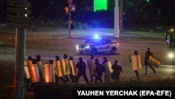 Riot police advance along a street in Minsk in the early hours of August 12.