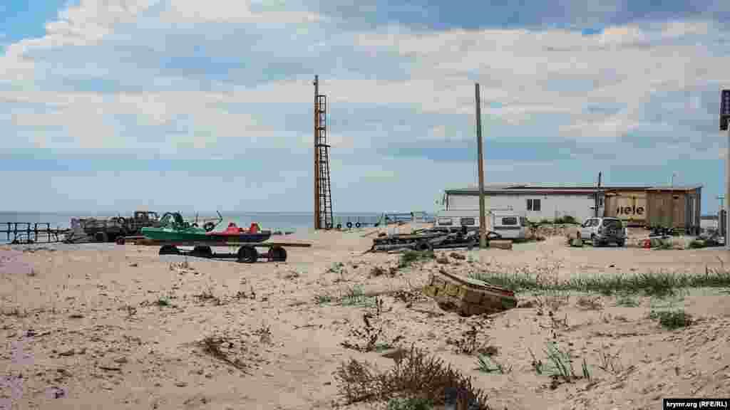 Причал местного лодочного кооператива в окружение песчаных штормовых наносов, похожих на небольшие дюны