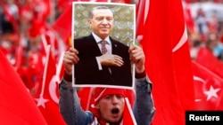 Түрк президент Эрдоганды колдогон акцияда анын сүрөтүн кармап турган демонстрант. 31-июль,