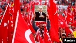Germany, Cologne, a supporter of Turkish President Tayyip Erdogan holds up a picture during a pro-government protest 311ju1l2016