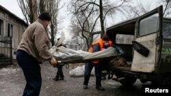 Жители погружают тело убитого во время ракетного обстрела в Донецке, 1 февраля 2015 года.