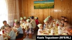 Софронийдің паналау орнында балалар тамақ ішіп отыр. Алматы облысы, Түймебаев кенті, 24 шілде 2013 жыл.