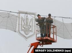 Muncitori instalând decorațiuni cu tridentul ucrainean, Kiev, 2014.