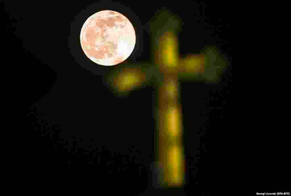 The last full moon of this year, also known as the Cold Moon, rises from the clouds above the Orthodox Church of St. John the Baptist in Skopje on December 30. (epa-EFE/Georgi Licovski)