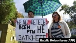 """A woman holds a sign reading """"You can't shut up everyone!"""" as journalists and supporters take part in a protest against the list of """"foreign agent"""" media in central Moscow on September 4."""