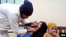 A Pakistani health worker administers a polio vaccine to a child.