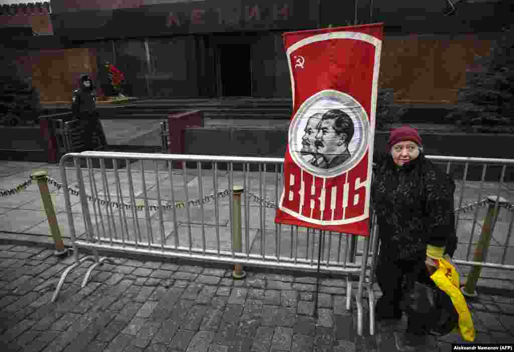 A Russian Communist Party supporter holds a banner with portraits of Soviet leaders Vladimir Lenin and Josef Stalin during a memorial ceremony at Stalin's tomb on Red Square in Moscow on March 5. (AFP/Aleksandr Nemenov)