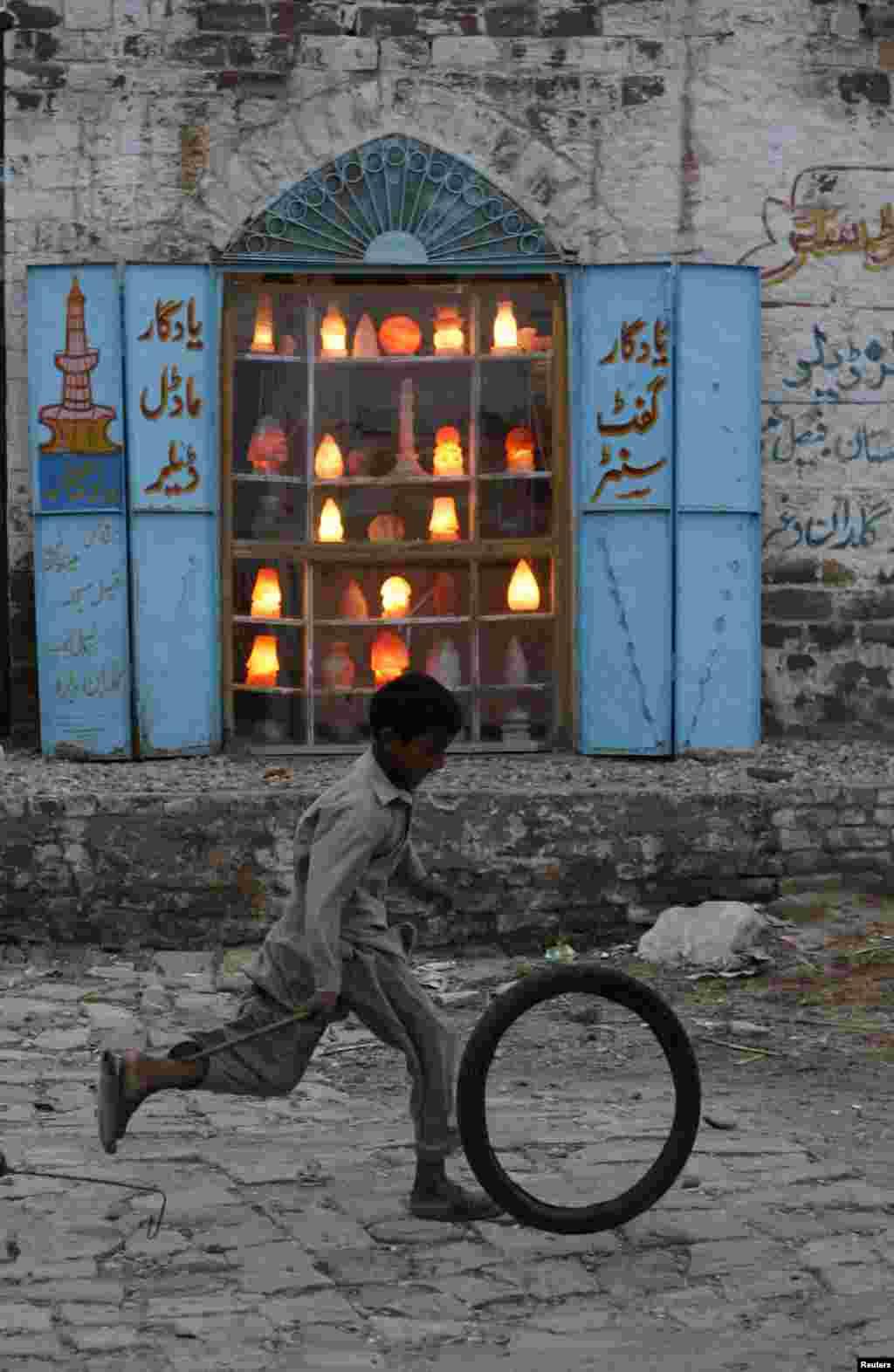 A Pakistani boy runs past a shop selling lamps and decoration pieces.