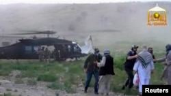 In this still image from a video released in June 2014, Blackhawk helicopter waits as U.S. Army Sergeant Bowe Bergdahl (2nd R, back facing) is being led to the American military during his release at the Afghan border.