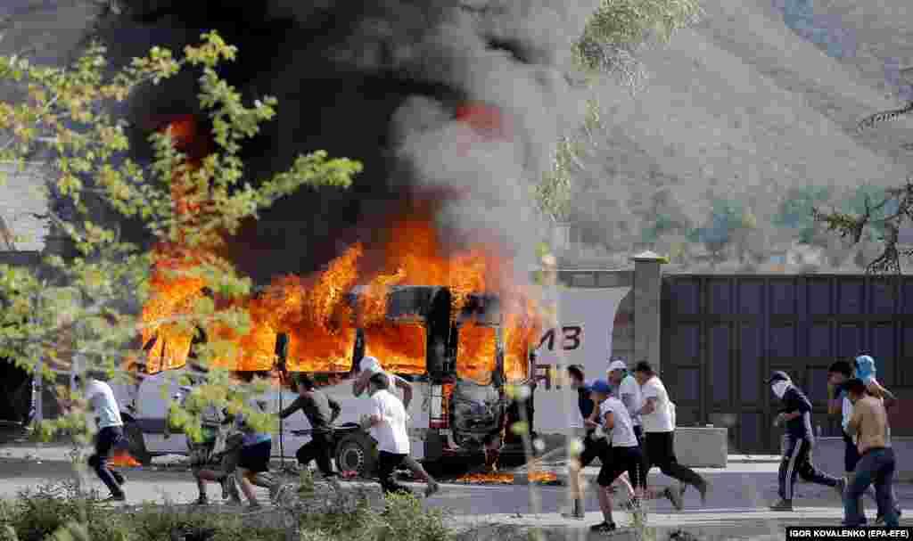 Atambaev supporters run past a flaming vehicle in Koi-Tash village.