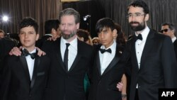 Actors Fawad Mohammadi (second from right) and Jawanmard Paiz (left) arrive with director Sam French (second from left) and producer Ariel Nasr on the red carpet for the 85th annual Academy Awards.
