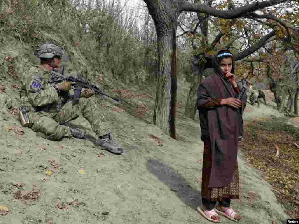 A U.S. soldier takes position as an Afghan girl stands next to him during a patrol as part of an overall security and disruption insurgency mission in Wardak Province on November 17. (REUTERS/Umit Bektas)