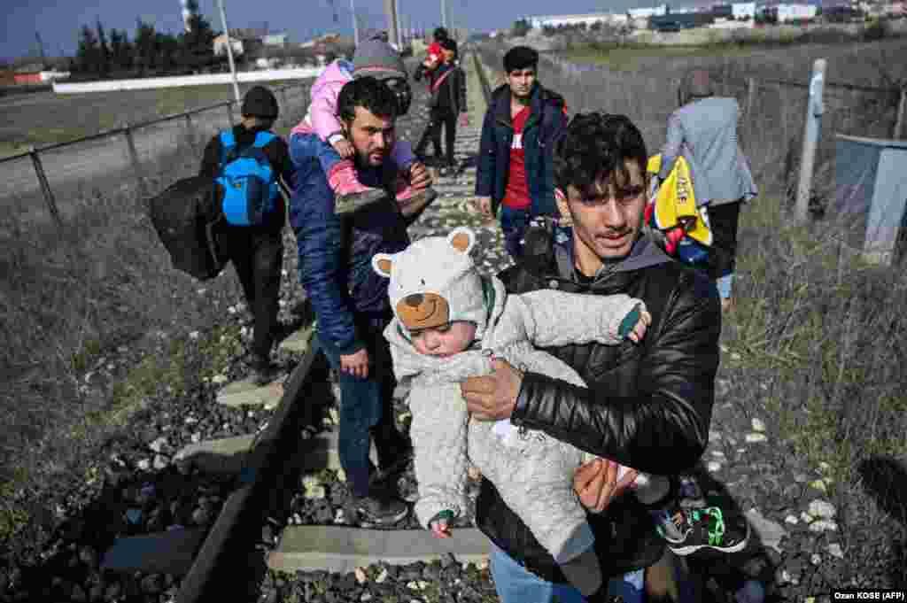 Поток людей с детьми направляется к реке Мерич рядом с городом Эдирне.