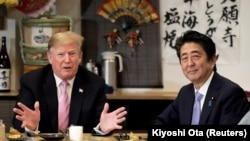 U.S. President Donald Trump talks with Japanese Prime Minister Shinzo Abe during a couples dinner with first lady Melania Trump and Abe's wife Akie in Tokyo, May 26, 2019