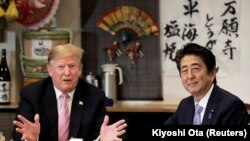 U.S. President Donald Trump talks with Japanese Prime Minister Shinzo Abe during his visit, May 26, 2019.