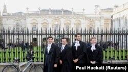 Выпускники Кембриджского университета позируют после церемонии вручения дипломов.