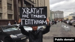 Гражданский активист Ринат Кибраев стоит с плакатом у здания Государственной думы России. Москва, 30 сентября 2013 года.