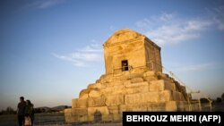 An Iranian family poses for a picture on May 19, 2015, next to the tomb of Cyrus the Great of Persia.