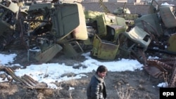 Afghan man surveys a warehouse containing scraps of Soviet-era military vehicles and tanks in Kabul