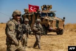 Америкалық әскерилері Түркияның әскери көлігінің жанынан өтіп барады.