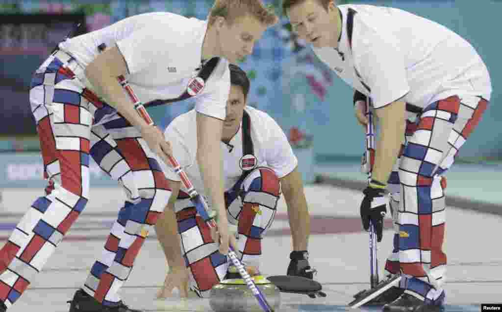 Norway's skip Thomas Ulsrud (center) watches his shot as teammates Haavard Vad Petersson (left) and Christoffer Svae sweep during their men's curling round-robin game against the United States in the Ice Cube Curling Center.