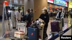 Disa pasagjerë në një aeroport në Kinë.