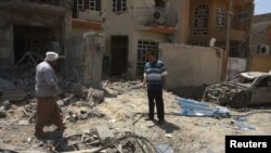 Banorët lokalë në vendin e një eksplodimi të mëparshëm me bombë në qytetin Taxhi të Irakut