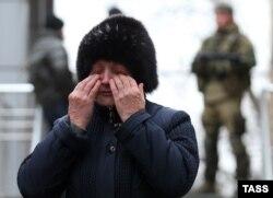 """Родственница одного из шахтеров. На заднем плане – вооруженные сепаратисты так называемой """"ДНР"""""""