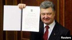 Президент Петро Порошенко демонструє підписаний закон про ратифікацію Угоди про асоціацію з Євросоюзом