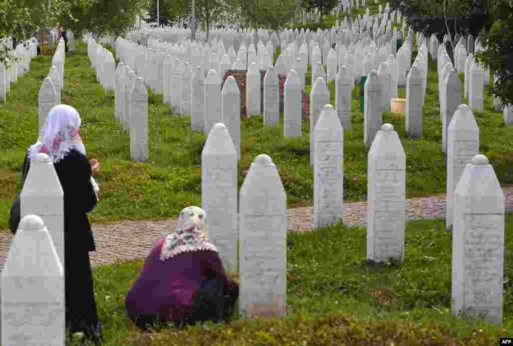 Боснийские мусульманки у могил родственников на мемориальном кладбище в деревне Поточари близ Сребреницы
