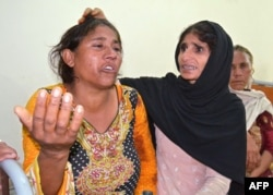 A Pakistani woman comforts a mourner after the death of a relative in the bomb attack . (file photo)