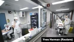 Hordágyas mentősök egy koronavírusos beteg szállítására várnak egy brüsszeli klinikán 2020. október 28-án.