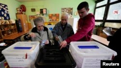 Macedonians cast their ballots in local elections at a polling station in Skopje on March 24.