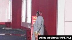 Пенсионерка просит милостыню возле магазина в Актобе. Октябрь 2009 года.