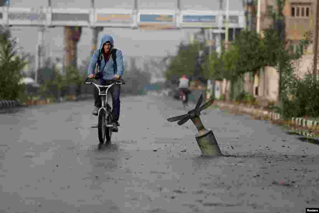 A Syrian man rides his bicycle near what activists said was an exploded cluster bombshell in Damascus on November 5. (Reuters/​Bassam Khabieh)