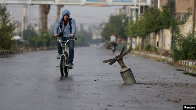 A resident rides his bicycle near what activists say is an exploded cluster-bomb shell in the Syrian town of Douma in November.